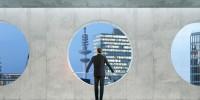 Mann vor einer Mauer mit runden Durchbrüchen im Hintergrund die Ansicht einer Stadt